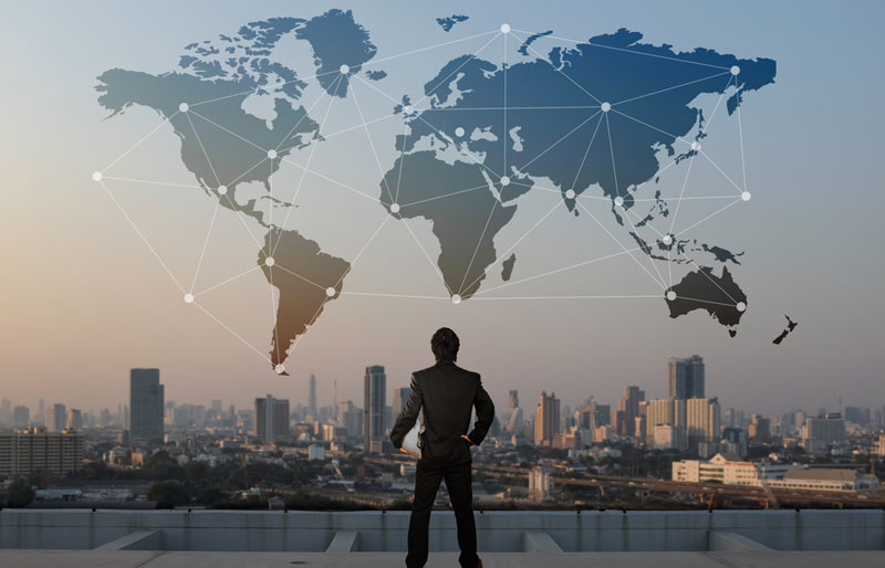 businessman starting at the city view with continents as an overlay