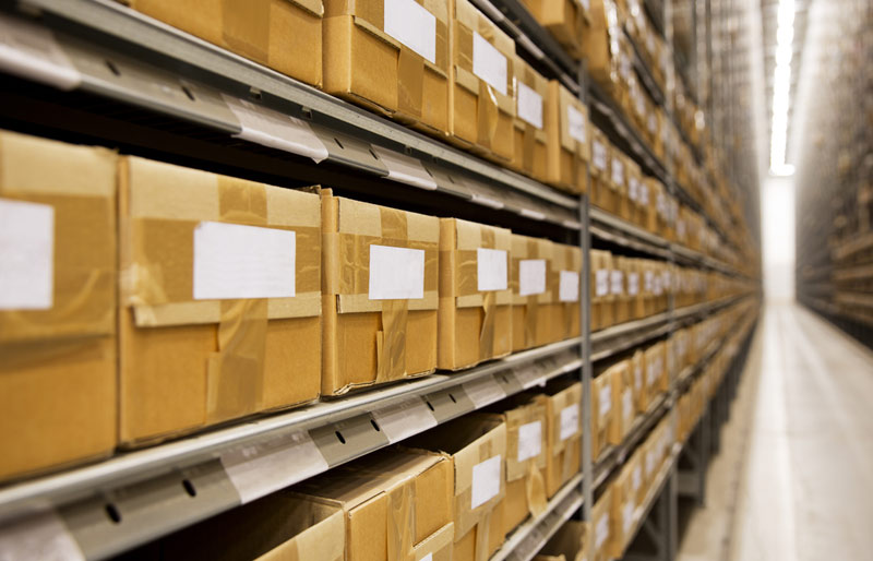 Rows of boxes on shelves in warehouse ready for shipping
