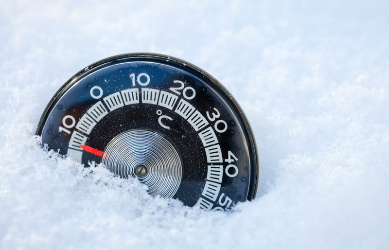 Circular thermometer sitting in snow with a -10 degrees celcius reading