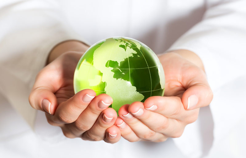 Woman holding green coloured globe in her hands