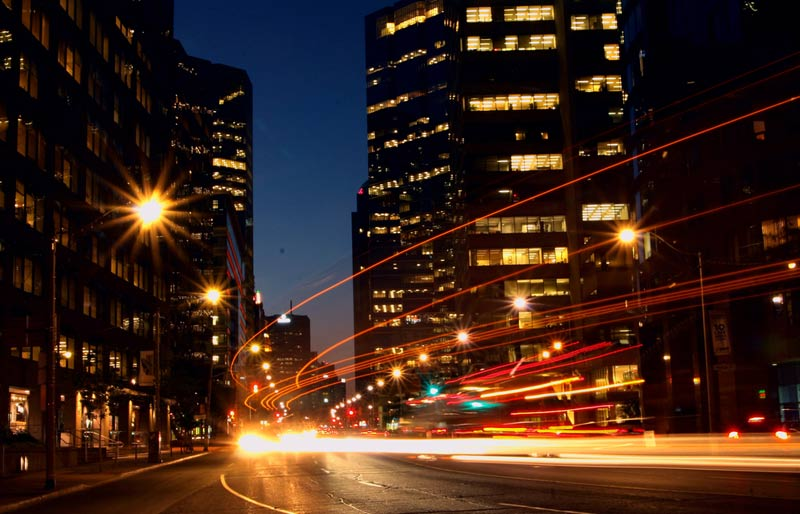 An image of a city at night taken with a slow shutterspeed showing the streaks of the cars light.