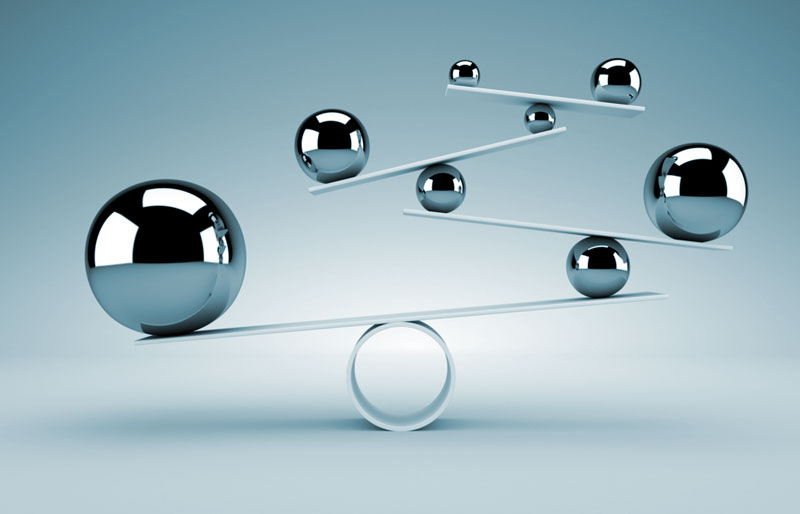 A balancing act concept image using Teeter Totters and different sized ball bearings.