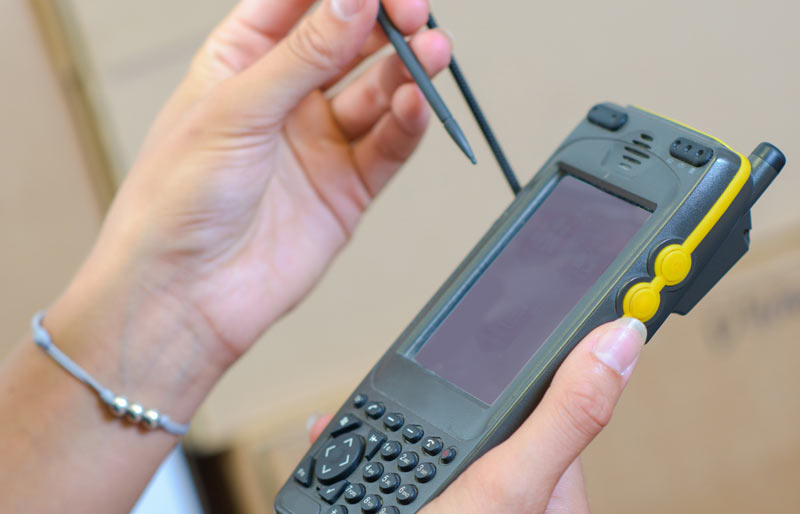 A close-up image of a female business professional using a handheld inventory computer.