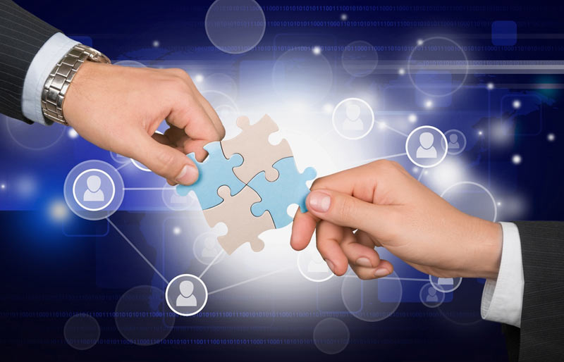A concept image of two business professionals connecting puzzle pieces with interconnecting people icons.