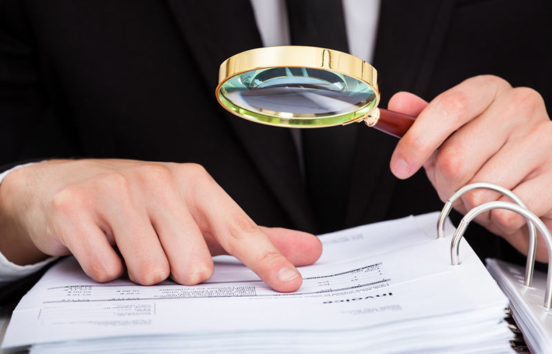 Business person looking at document through magnifying glass.