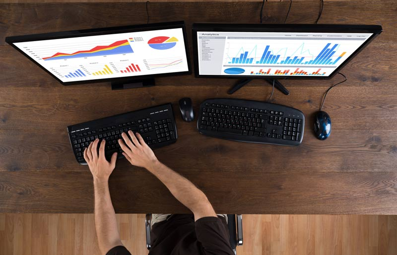 audit data analytics alerts, hand typing in front of two monitors