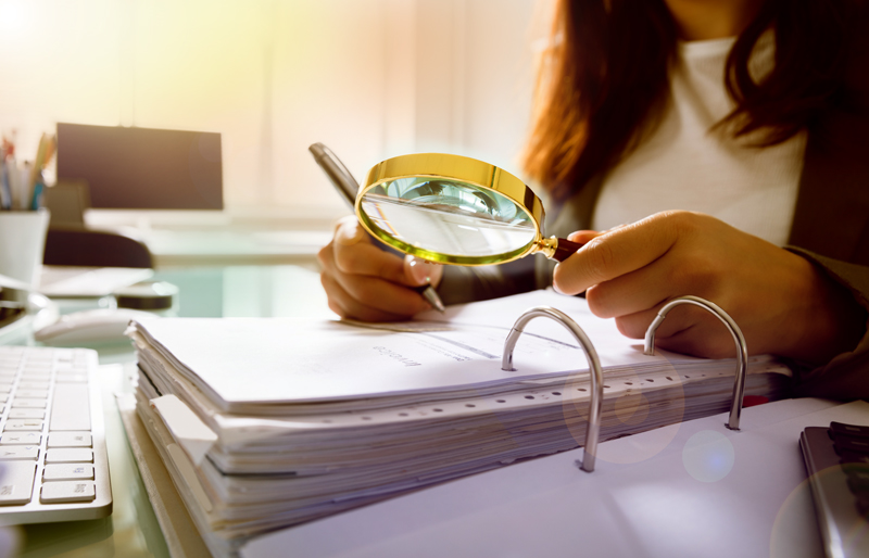 Businesswoman using a magnifying glass to look over a large binder of business documents