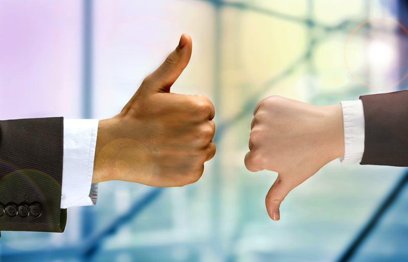 The hands of two separate business people, one giving a thumbs down, the other thumbs up