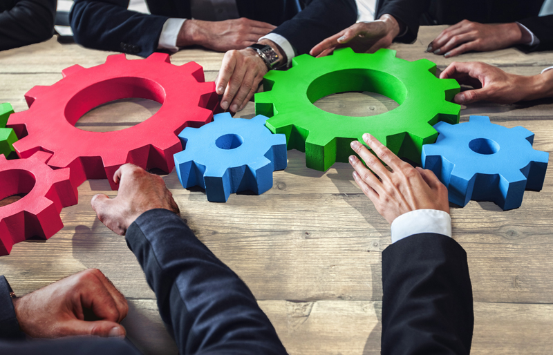 A group of business people examining the model of several cogs connected together