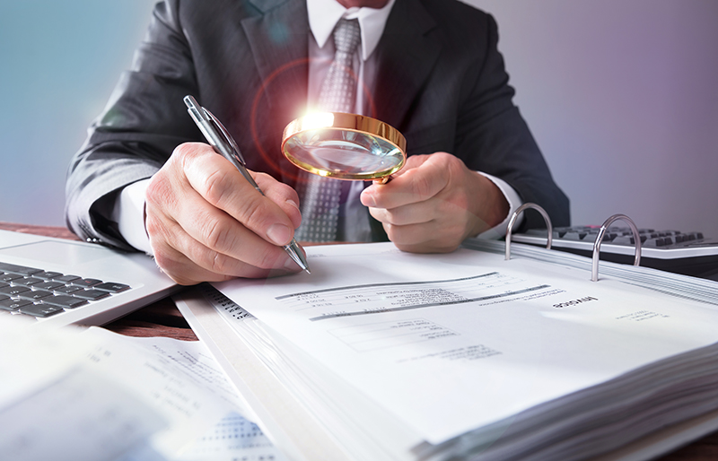 Business person using a magnifying glass to look at large book of business documents.