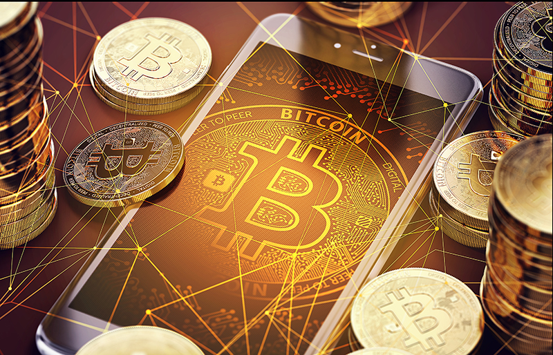 Bitcoin logo displayed on smart phone screen, surrounded by stacks of bitcoins