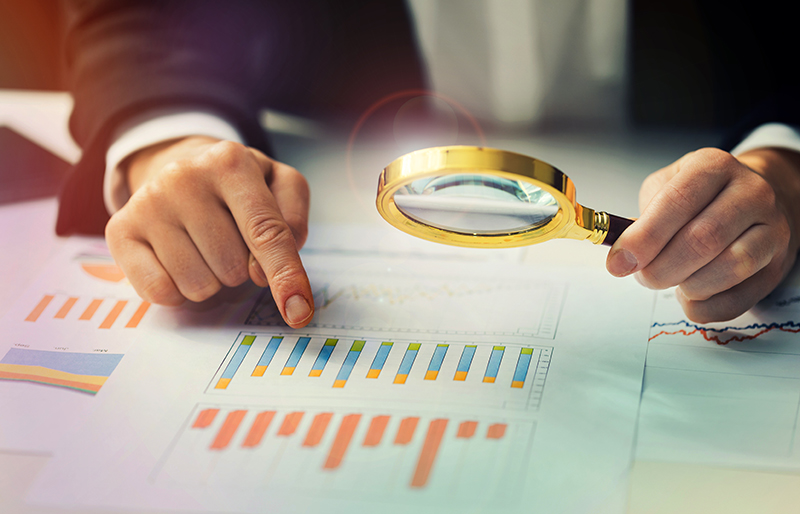Business person using a magnifying glass to examine business documents