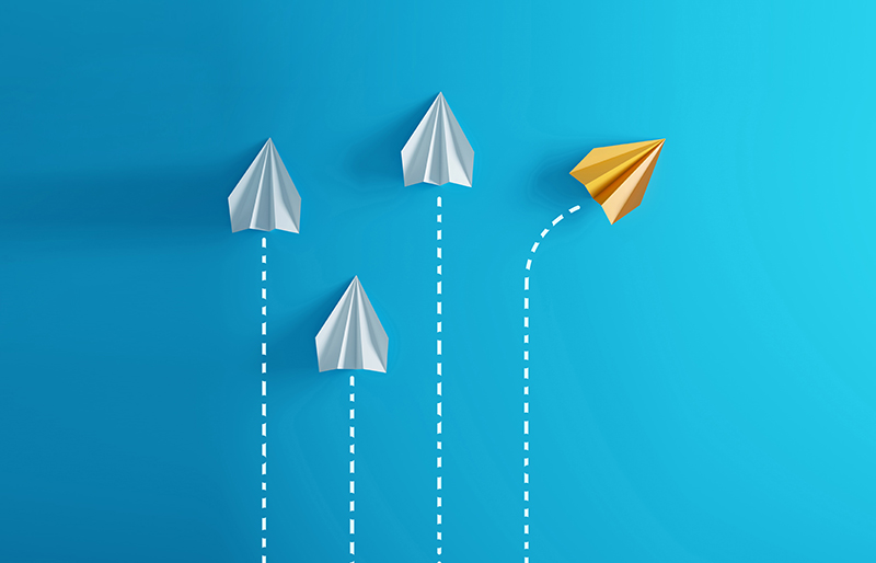 Three white paper airplanes with dotted-lines indicating a straight path, with a fourth orange airplane with a dotted-line changing direction