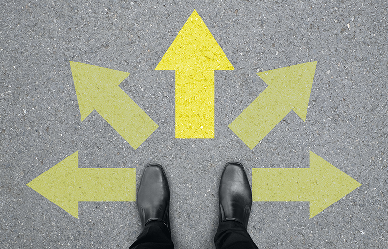 Shoes of business person standing on asphalt, with multiple arrows pointing in different directions, and one brighter and bigger then the others