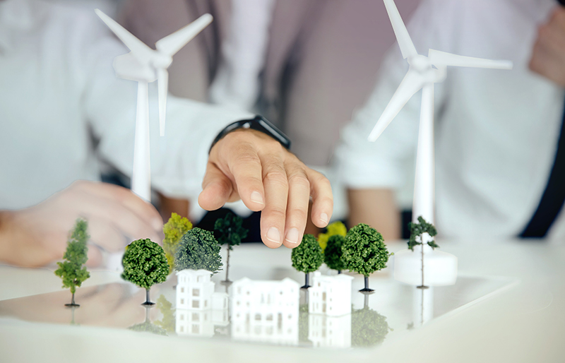 two people urban planning using windmills and miniature models of trees and buildings