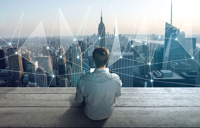 Man with laptop looking at cityscape with overlay of lines connecting various buildings together.
