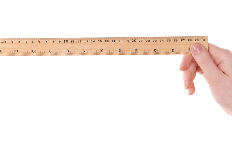 A hand holding up a wooden ruler.
