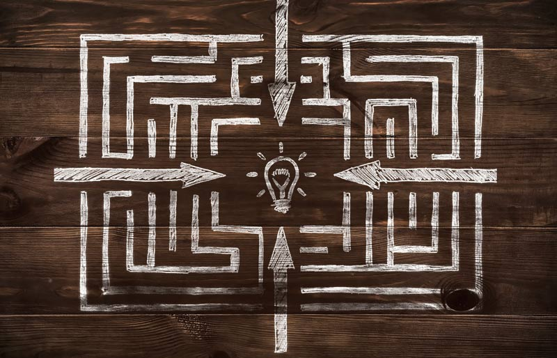 A drawn maze with directions pointing to the centre. A light bulb is in the centre.
