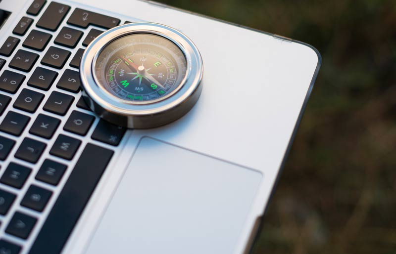 A compass on top of a laptop.