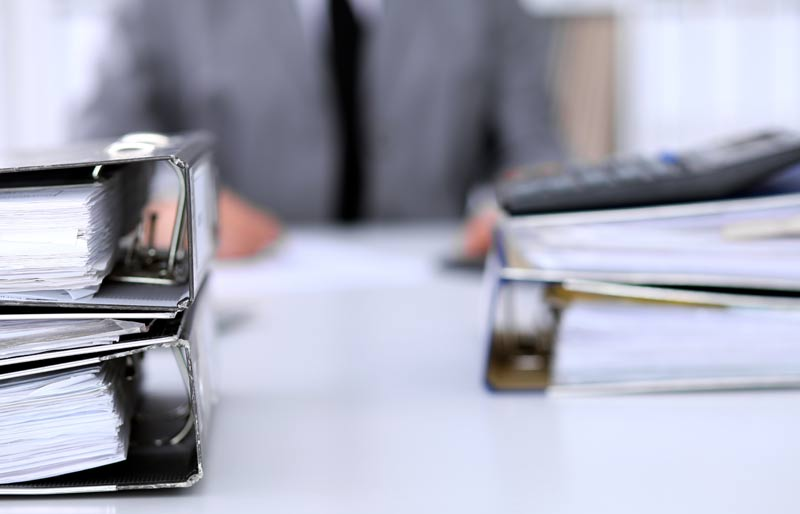 Binders with papers on desk with blurred out businessman in the background.