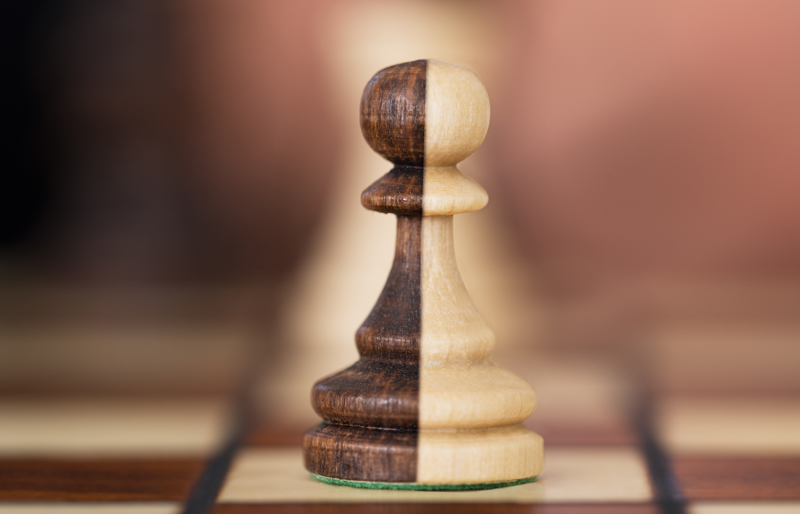 Close-up of a two-coloured chess piece on a chessboard.