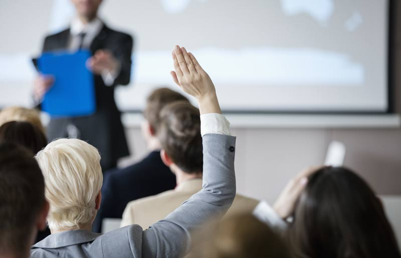 woman raising hand with question in a seminar
