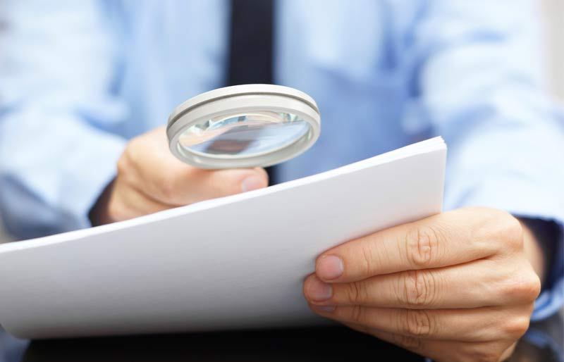 Male accountant looking at a file through a magnifying  glass.