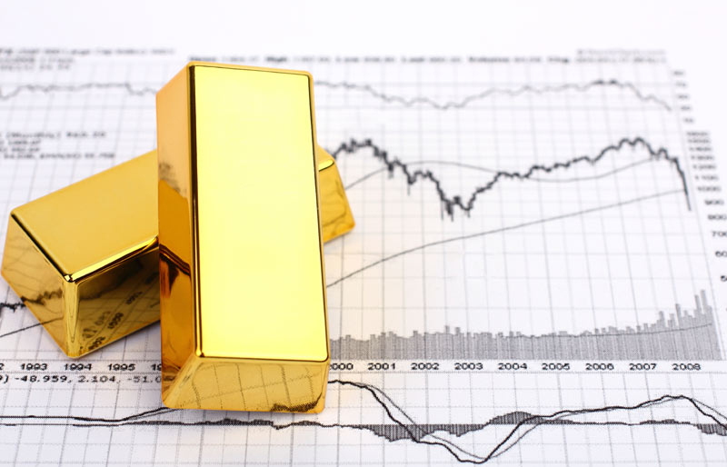 Gold bars sitting on printed financial charts