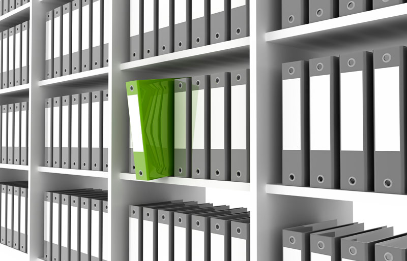 A photograph of shelving holding grey binders with one green one pulled out half way.
