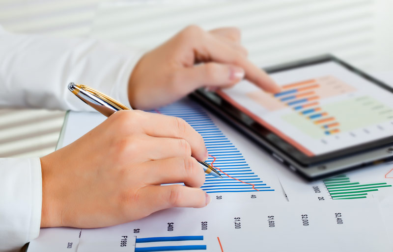 A cropped image of a female business professional working on financials.