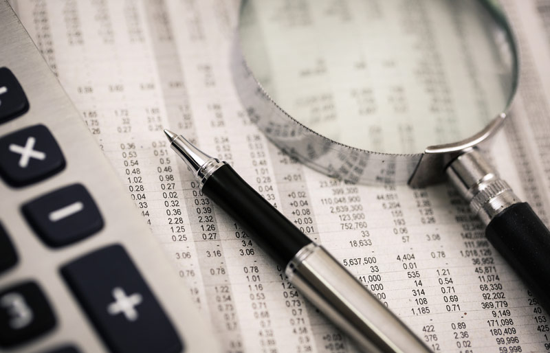 A close-up of a calculator, a pen and a magnifying glass on financials.