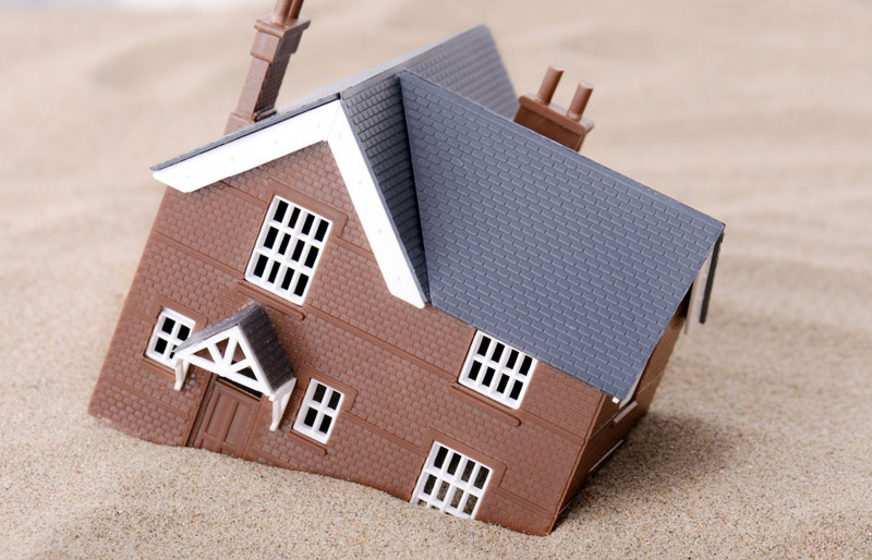 Toy house sinking in sand