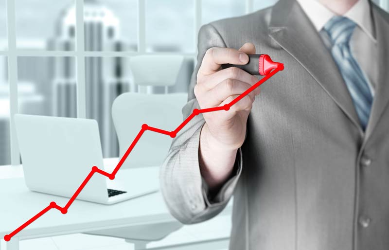 Male accountant drawing a red line graph on glass.