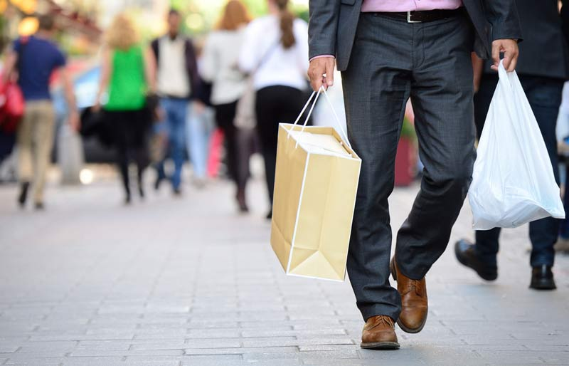 Male business professional walking on sidewalk carrying shopping bags.