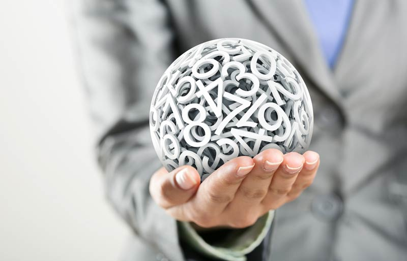 A business professional holding a small globe formed with numbers.