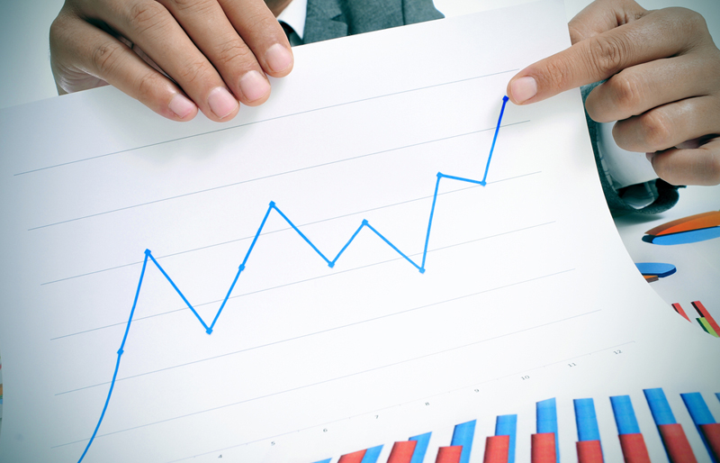 A close-up image of a male business professional holding up a line graph and pointing to the upturn in revenue.