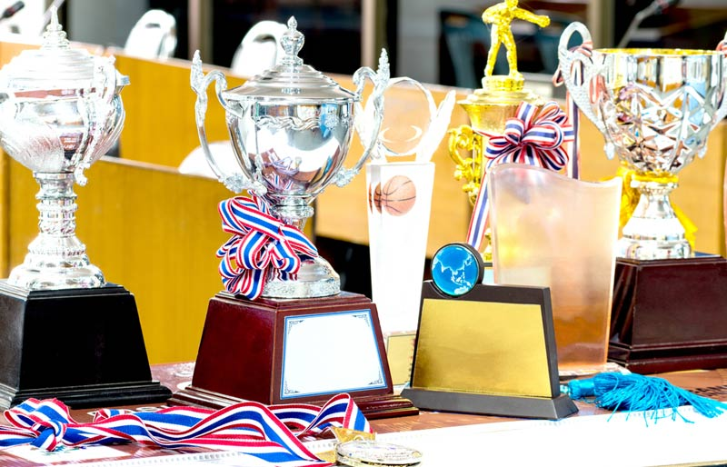A photograph of various trophy's and medals sitting on a desk.