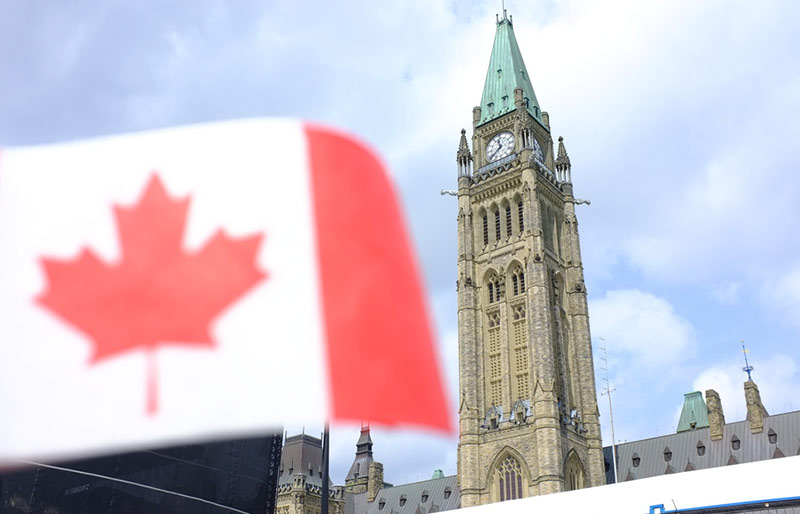 Canadian flag with the parliament on the background.