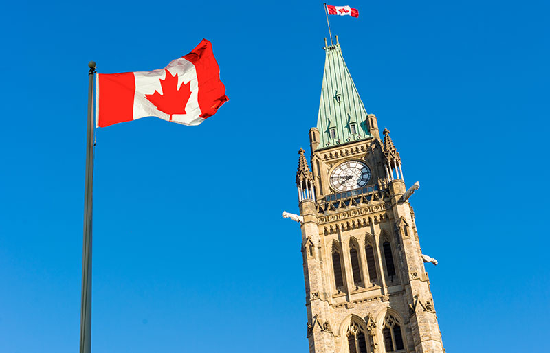 Canadian flag with Parliament buildings in background