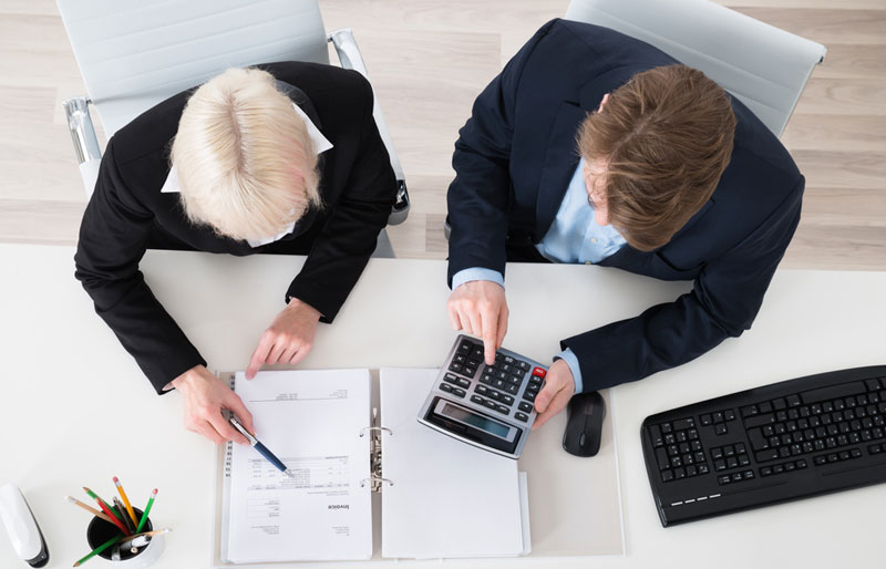 two business people using a calculator and looking at notes