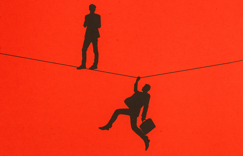 Silhouette of business person standing on  a tight-rope wire, while another business man hangs from the wire against a red background