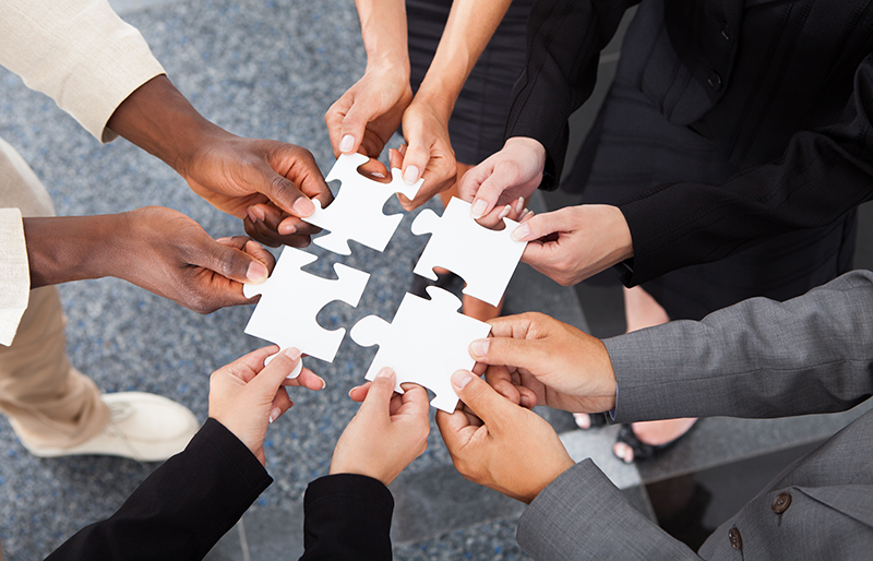 Hands of several business people each holding a puzzle piece to make one large piece