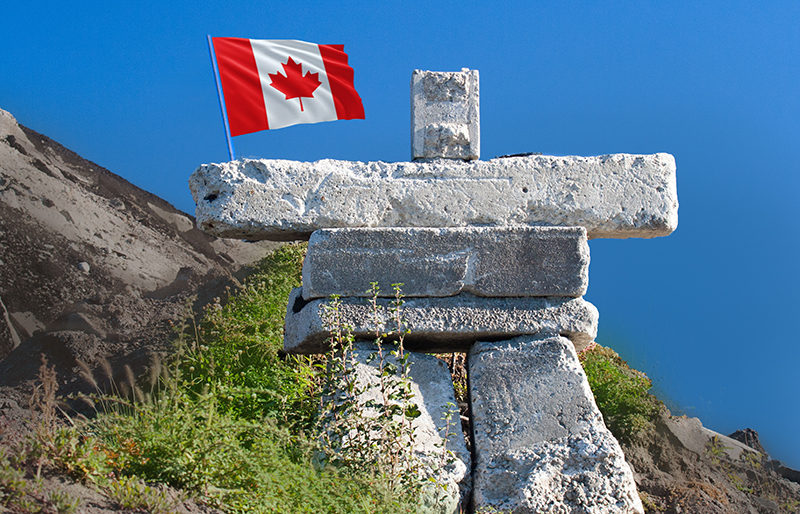 Inuksuk landmark with a Canadian Flag among a Northern Canada environment