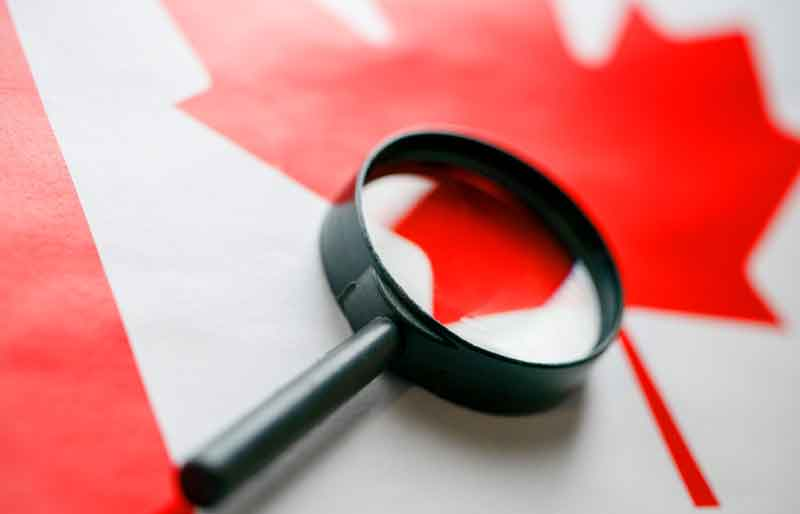 The flag of Canada looks through a magnifying glass