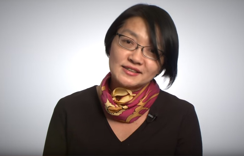 Photo of Asian woman wearing glasses against a grey background.