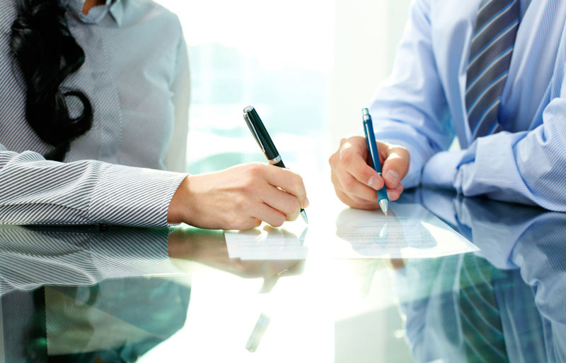 Business woman and man writing on document in meeting room