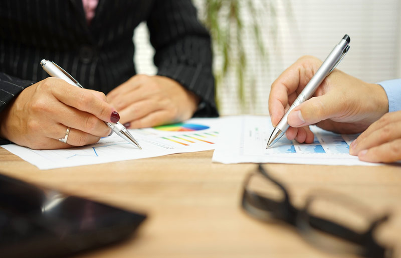 A close-up image of a female and male business professional at a table reviewing various reports.