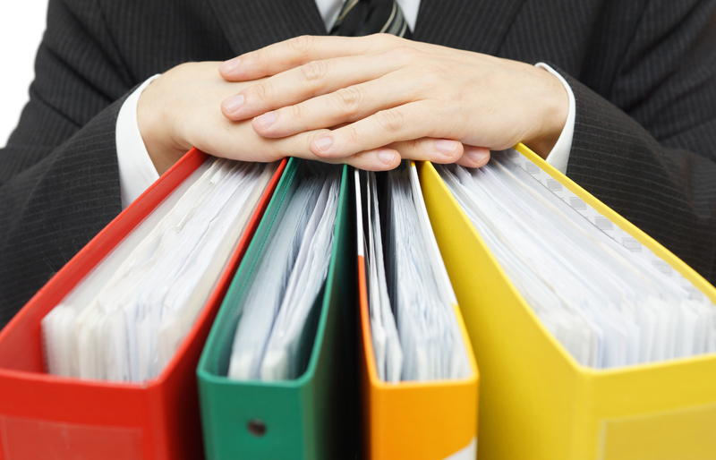 Hands of a business person resting upon three binders representing the auditing standards, as if in a discussion
