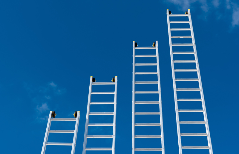 Four ladders reaching up in to the sky at different heights, resembling a business bar chart