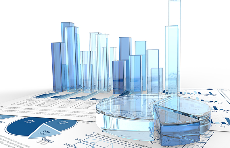 Various business graphs made of transparent coloured glass, sitting on various business documents
